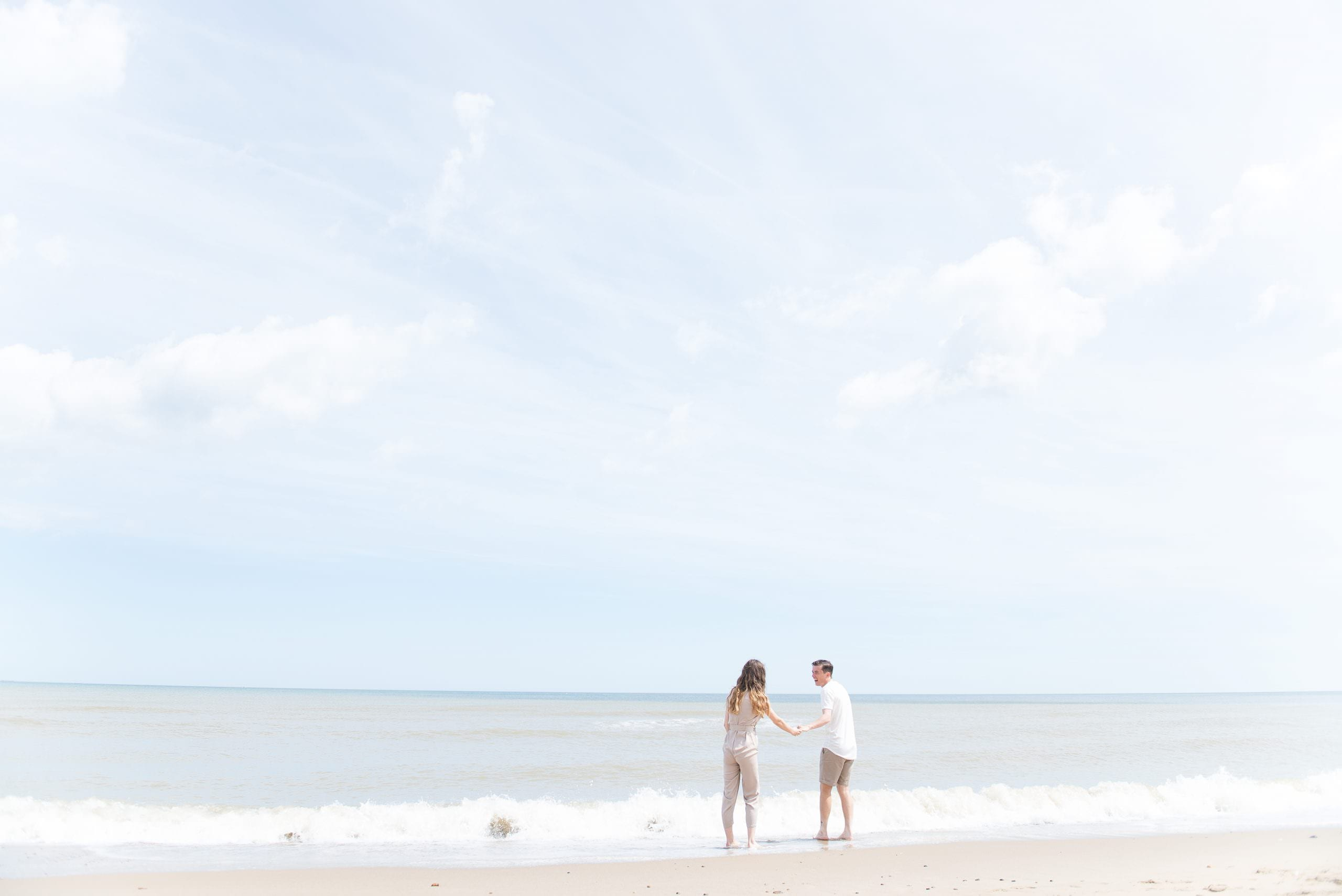 Engaged couple splashing in the sea at Happisburgh Beach in Norfolk