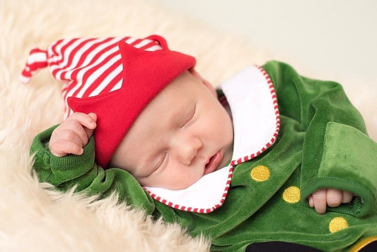 Newborn baby boy sleeping in his adorable elf outfit